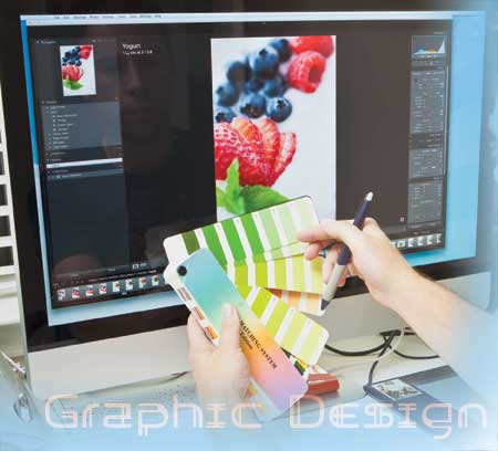 graphic design solutions - graphic designer at computer with pantone chart